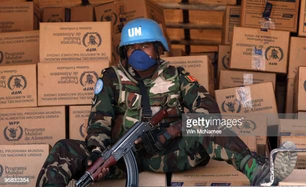 Peacekeeper guards food supplies to be distributed by the World Food Program on January 17, 2010 in Port-au-Prince, Haiti. Aid agencies are...