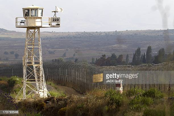 A UN peacekeeper keeps watch from an observation tower near the Quneitra crossing in the demilitarized United Nations Disengagement Observer Force...