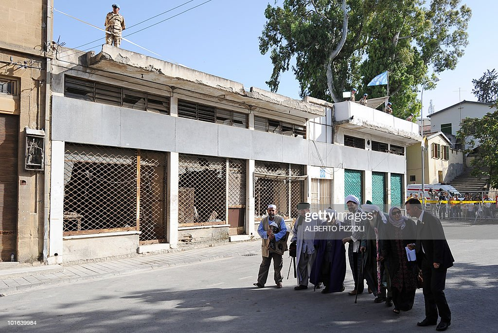 UN peacekeepers in blue berets watch from above as Muslim clergymen, including sufi mystic Sheikh Nazim (3rd R), walk towards Nicosia's Latin Holy Cross Church on the Green Line in the divided capital of Cyprus to meet Pope Benedict XVI on June 5, 2010, on the second day of the pontiff's visit to the mainly Greek Orthodox east Mediterranean island.
