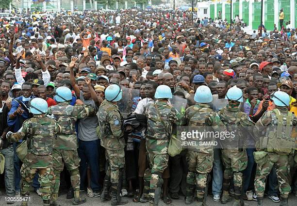 Peacekeepers try and control Haitians queueing for aid at a distribution point outside the Presidential palace in Port-au-Prince on January 25, 2010....