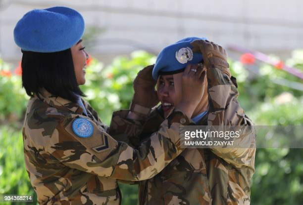 A UN peacekeeping force in Lebanon liaison fixes her colleagues hat as they attend the UNIFLIS's 40th anniversary celebration at its base in...