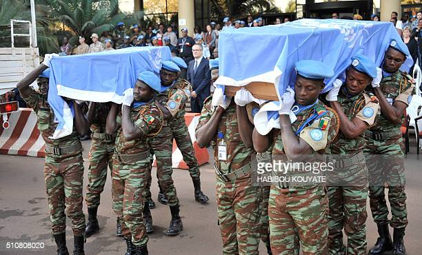 UN peacekeeping force soldiers carry coffins covered with United Nations flag at Bamako on february 17 at the last tribute to seven guinean UN...