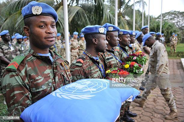 UN peacekeeping force soldiers carry cushion and flowers at Bamako on february 17 during the last tribute to seven Guinean UN soldiers killed on...