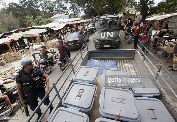 Peacekeeping police from Portugal guard a truck convoy as they bring ballot boxes for distribution to districts amidst high tension one day before...