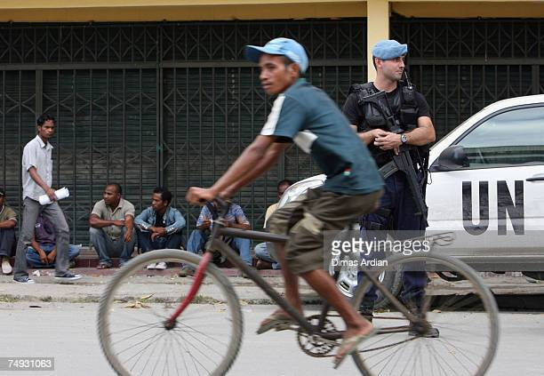 Peacekeeping Police Officer from Portugal stands guard as Fretilin supporters look on after a Fretilin campaign 3 days before election June 27 2007...