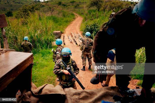 UN peacekeeping soldiers return to their patrol vehicle after dismounting to secure their vehicle while it crossed an unstablelooking bridge during a...