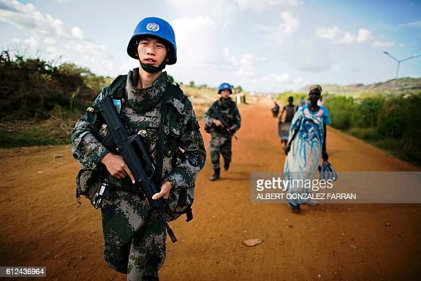 Peacekeeping troops from China deployed by the United Nations Mission in South Sudan patrol outside the premises of the UN Protection of Civilians...