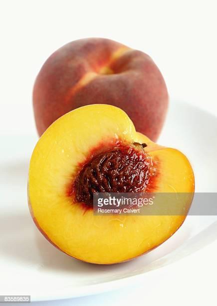 Peach and half a peach cut to reveal the stone.