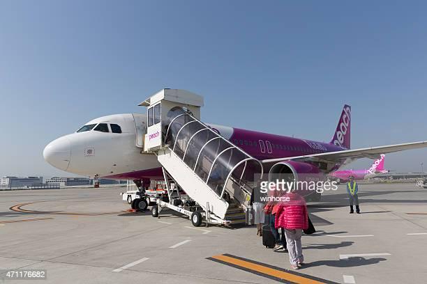 peach aviation airbus a320 - internationaler flughafen kansai stock-fotos und bilder
