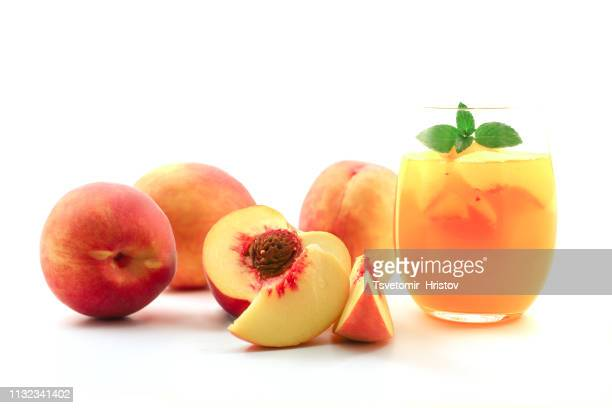 peach cocktail in glass with fresh fruit on white background. peach sangria. - モモ ストックフォトと画像