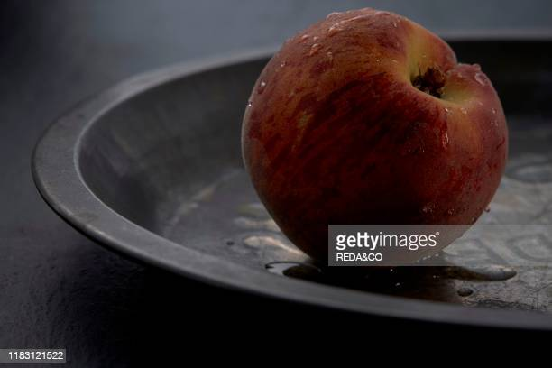 Peach fruit in a metal plate on a dark background