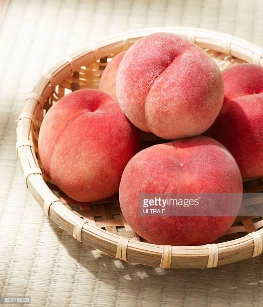 peach in basket - モモ ストックフォトと画像