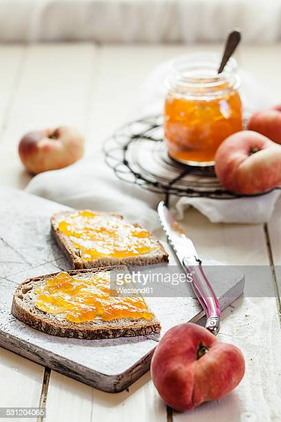 Peach jam on two slices of brown bread and doughnut peaches