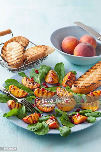 Peach salad garnished with pomegranate seeds and herb on plate