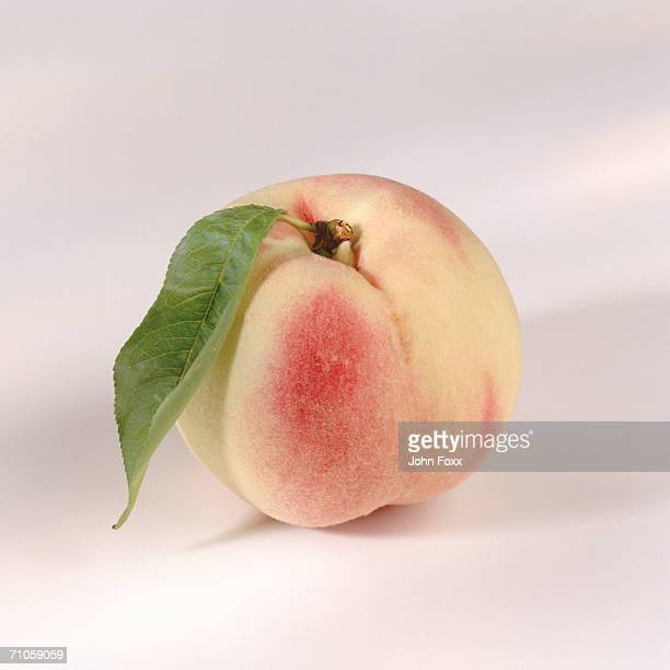 Peach with leaf on white background, close-up