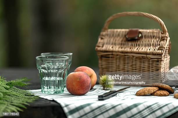 Peaches, glasses and picnic basket on table
