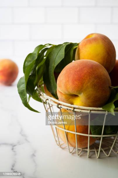 peaches on a kitchen counter - brycia james stock pictures, royalty-free photos & images