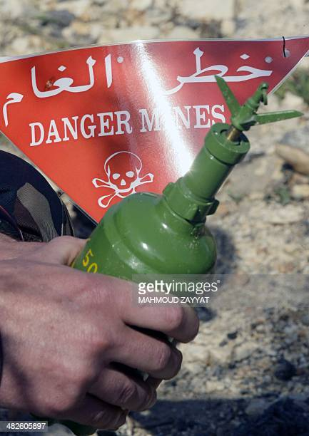 A peackeeper of the United Nations Interim Force in Lebanon shows a device on April 4 2014 during an awareness program on the dangers of landmines in...