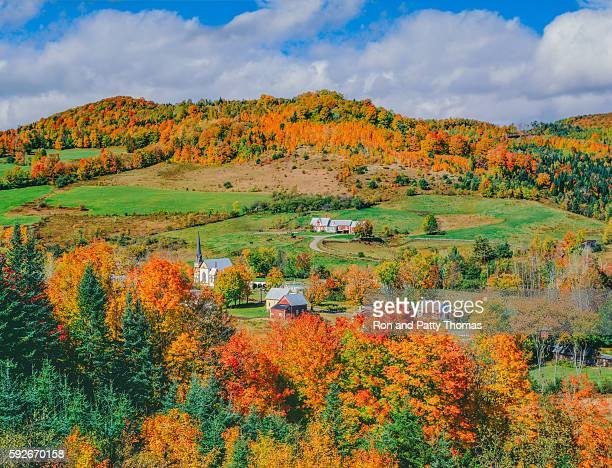 Peak autumn sugar maples with village in Vermont