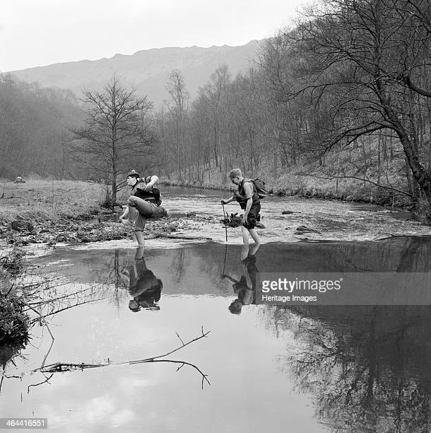 Peak District Derbyshire 1959 Two boys wading barefoot across a river in a valley with bare trees possibly Dove Dale with a dramatic hilly landscape...