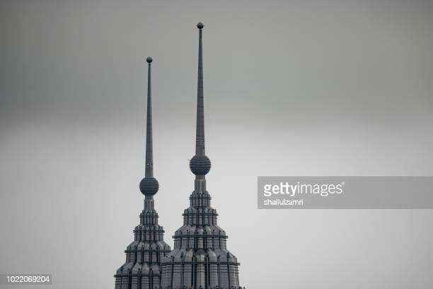 peak of petronas twin towers over cloudy and hazy day in kuala lumpur, malaysia. - torres petronas - fotografias e filmes do acervo