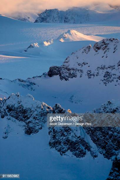 peaks of a snow covered mountain range glowing at sunset, kachemak bay state park - kachemak bay stock pictures, royalty-free photos & images