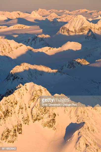 peaks of a snow covered mountain range glowing pink at sunset, kachemak bay state park - kachemak bay stock pictures, royalty-free photos & images