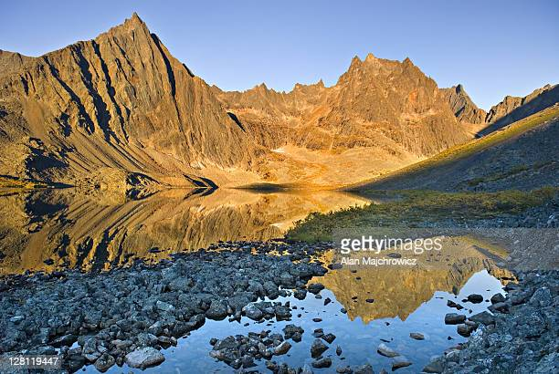 peaks of the tombstone range reflected in grizzly lake, tombstone territorial park, yukon, canada - territory stock pictures, royalty-free photos & images