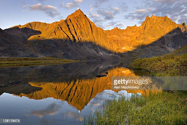 peaks of the tombstone range reflected in grizzly lake, tombstone territorial park. yukon, canada - territory stock pictures, royalty-free photos & images