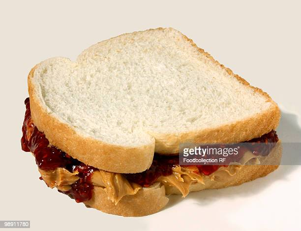peanut butter and jelly sandwich on white bread, close-up - peanut butter and jelly sandwich stock pictures, royalty-free photos & images