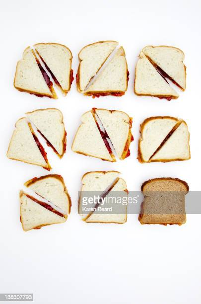 peanut butter and jelly sandwiches, one on whole wheat bread - peanut butter and jelly sandwich stock pictures, royalty-free photos & images