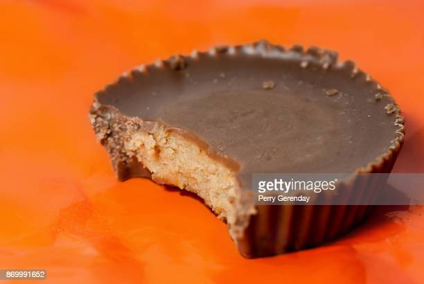 peanut butter cup with bite - halloween candy stock photos and pictures
