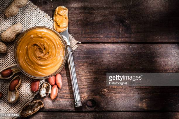 Peanut butter in a glass bowl shot on rustic wooden table