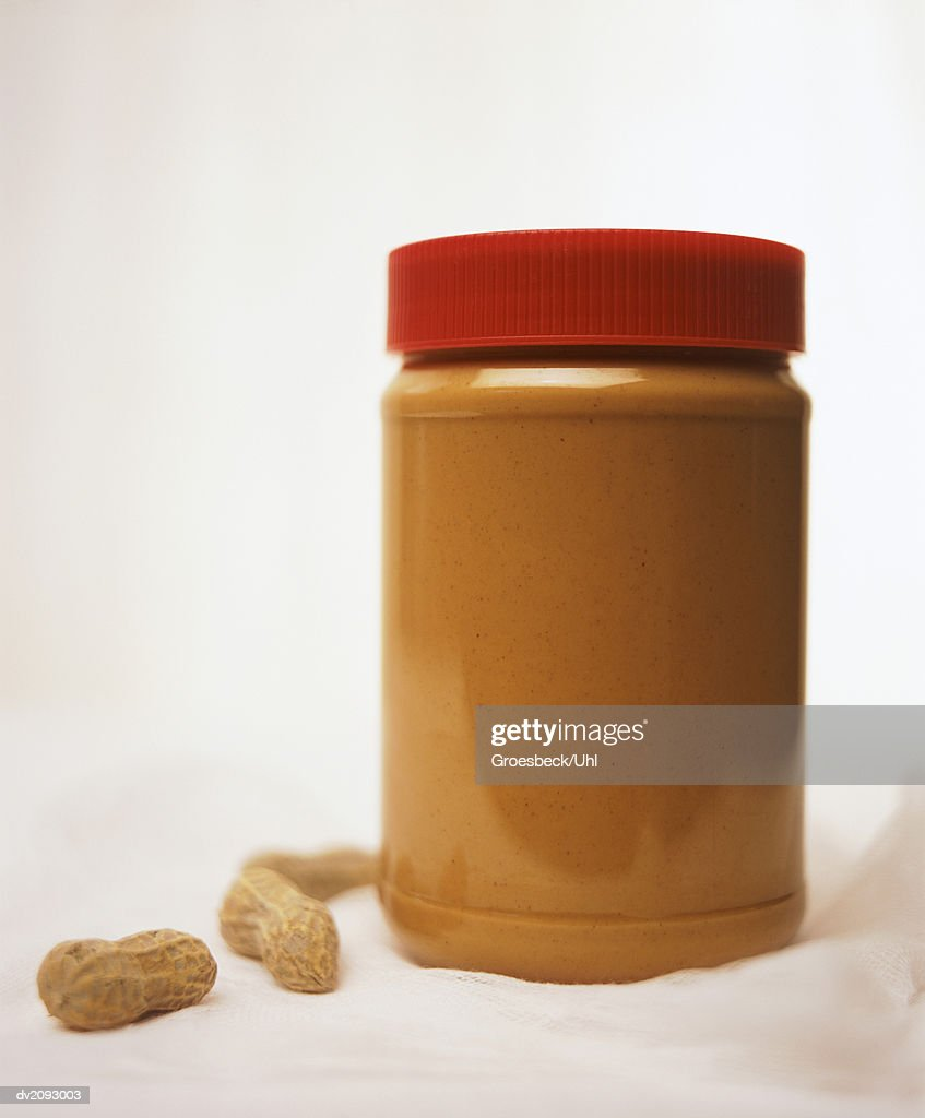 Peanut Butter Jar and Three Peanuts : Stock Photo
