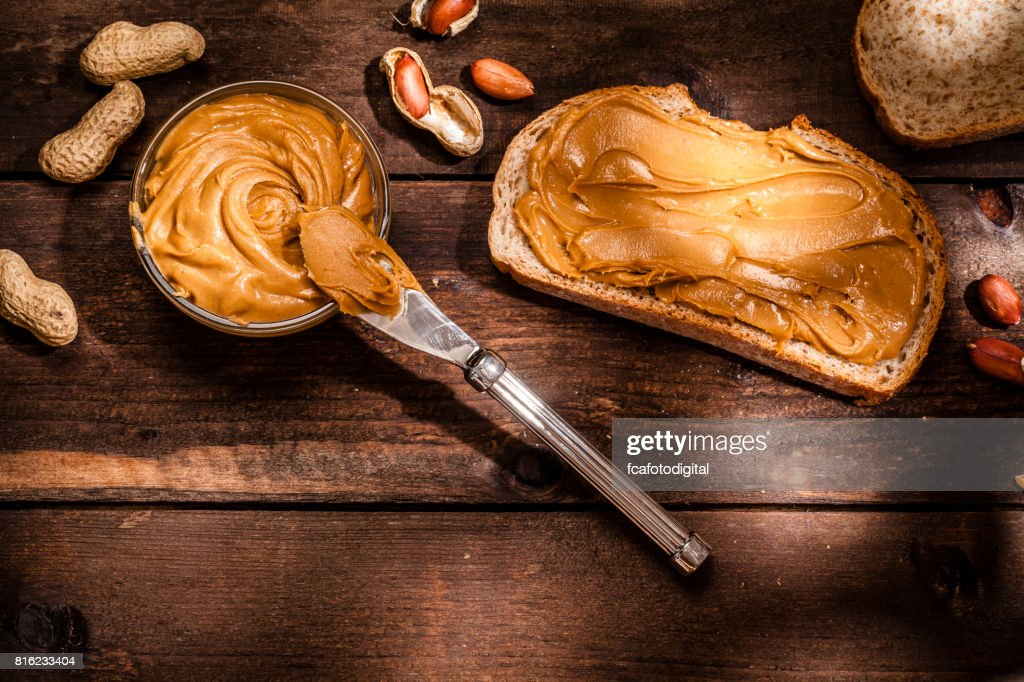 Peanut butter on bread slice shot on rustic wooden table : Stock Photo