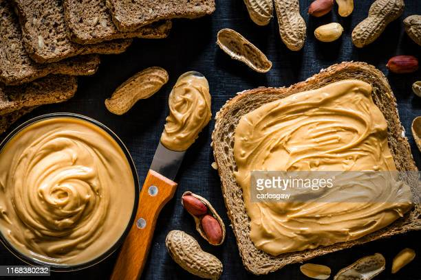 peanut butter scattered on a slice of bread - peanut butter stock pictures, royalty-free photos & images