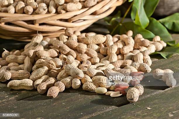 Peanuts -Arachis hypogaea- on a rustic wooden table