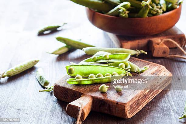 Peapods on wooden board
