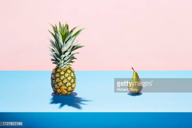 a pear and a pineapple meeting on a table top - still life not people stock photos and pictures