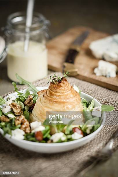Pear in puff pastry on salad with gorgonzola cheese in background