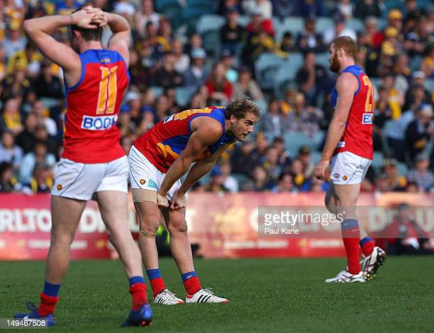 Pearce Hanley Joel Patfull and Daniel Merrett of the Lions look on as Jack Darling of the Eagles prepares to kick a goal during the round 18 AFL...