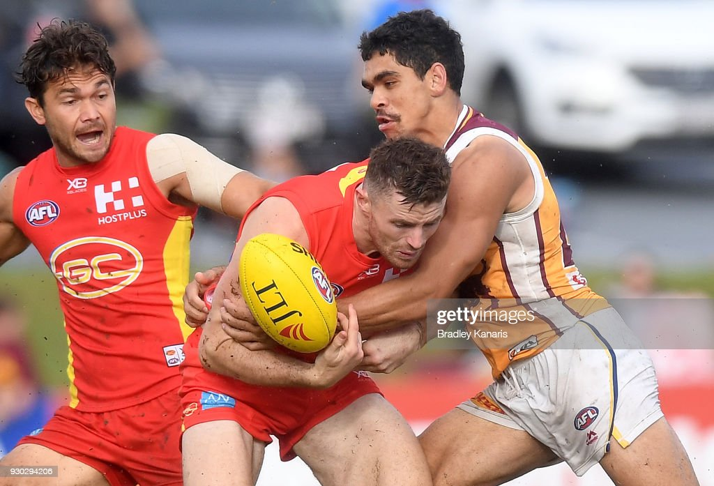 Pearce Hanley of the Suns is pressured by the defence of Charlie Cameron of the Lions during the JLT Community Series AFL match between the Gold Coast Suns and the Brisbane Lions at Fankhauser Reserve on March 11, 2018 in Brisbane, Australia.