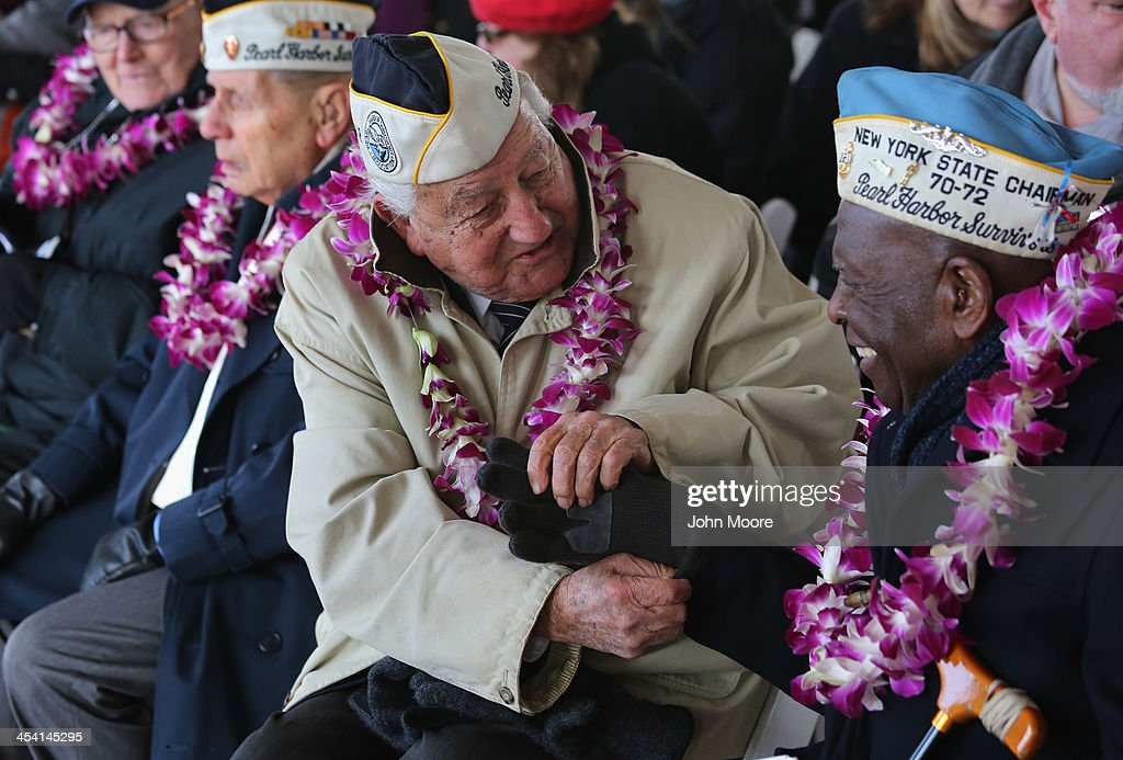 Pearl Harbor survivor Armando Galella, 92, helps fellow survivor Clark Simmons, 92, with his gloves at a ceremony marking the 72nd anniversary of the attack on Pearl Harbor, Hawaii on December 7, 2013 in New York City. Four Pearl Harbor survivors from the New York area gathered with former crew members of the USS Intrepid to mark the Japanese surprise attack on December 7, 1941 which killed 2,402 Americans and brought the United States into WWII.