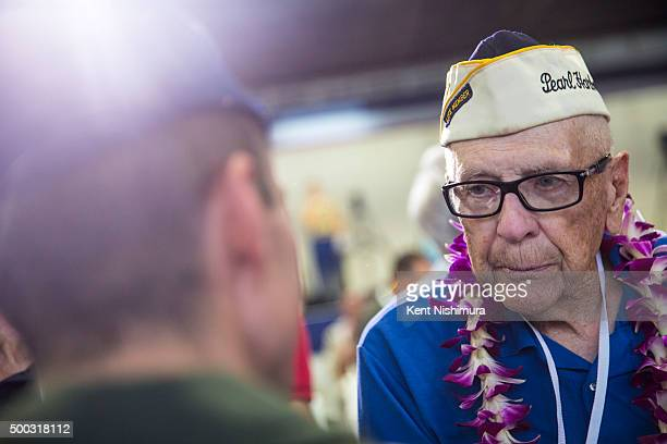 Pearl Harbor Survivor Charles Heite talks with Airman Kevin Hettinger during a memorial service marking the 74th Anniversary of the attack on the US...