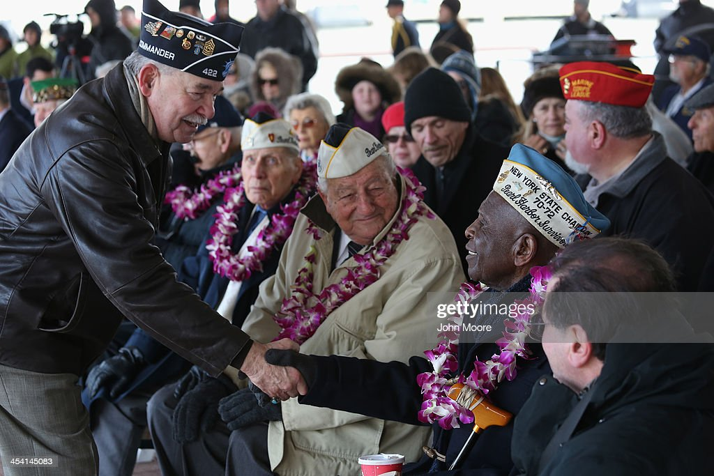 Pearl Harbor survivor Clark Simmons, 92, is congratulated after he spoke at a ceremony marking the 72nd anniversary of the attack on Pearl Harbor, Hawaii on December 7, 2013 in New York City. Four Pearl Harbor survivors from the New York area gathered with former crew members of the USS Intrepid to mark the Japanese surprise attack on December 7, 1941 which killed 2,402 Americans and brought the United States into WWII.