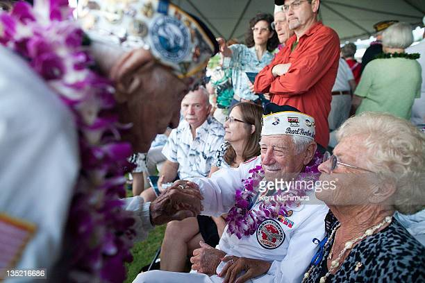 Pearl Harbor survivors Alan Bodenlos and Delton Walling greet each other before a memorial service for the 70th anniversary of the attack on the U.S....