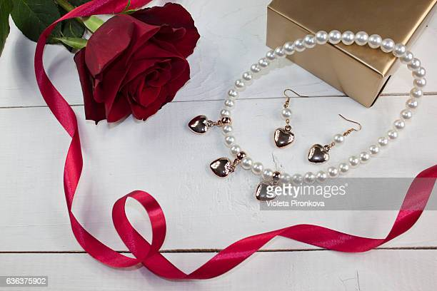 Pearl necklace and earrings with golden gift, red rose and red ribbon on white wood