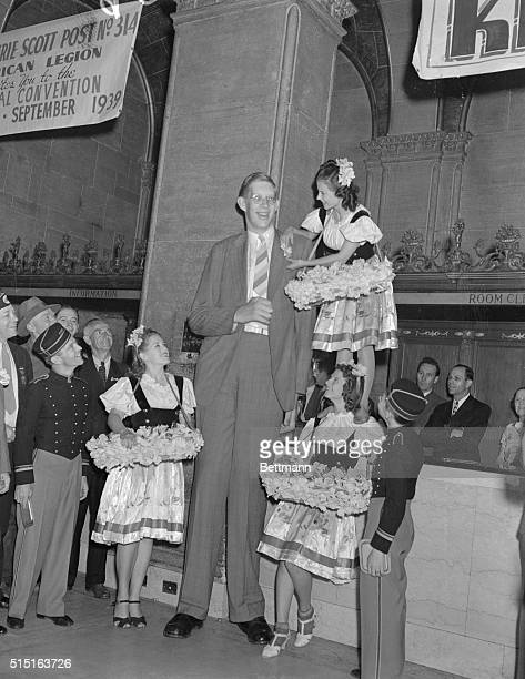 Pearl Tolson standing on the shoulders of another poppy girl pins a poppy on the lapel of Robert Wadlow 8foot 8 1/2 inch giant who has the...