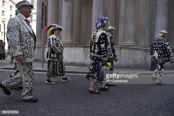 Pearly Kings and Queens walk past the church of England on their way to their service at St Mary Le Bow Church after the Harvest Festival service at...
