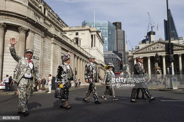 Pearly Kings and Queens walks past the church of England on their way to their service at St Mary Le Bow Church after the Harvest Festival service at...